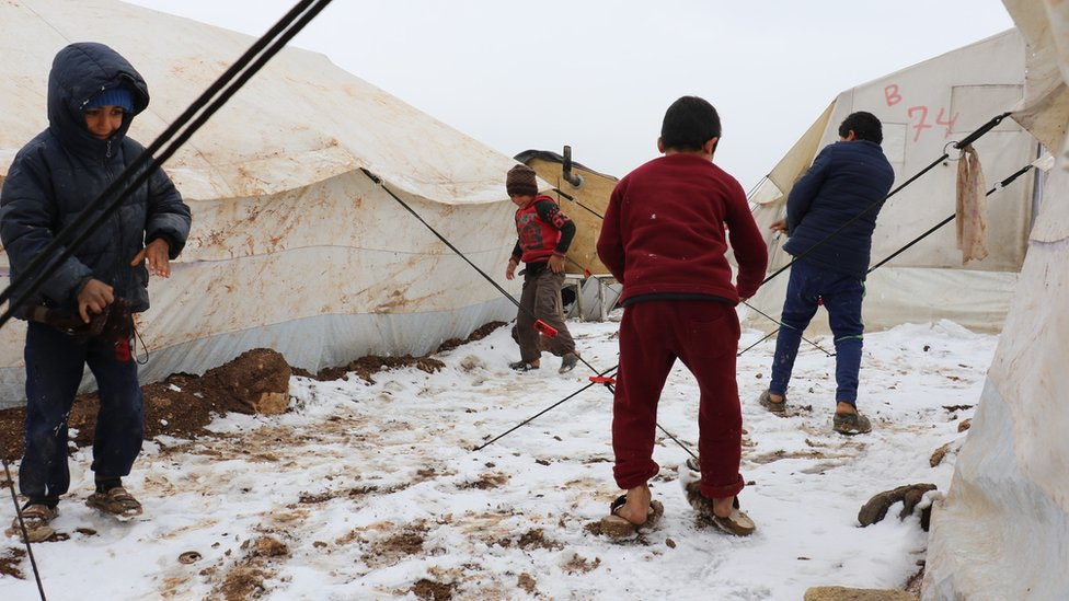 Children stand in the snow at a camp for displaced people in Aleppo province, Syria