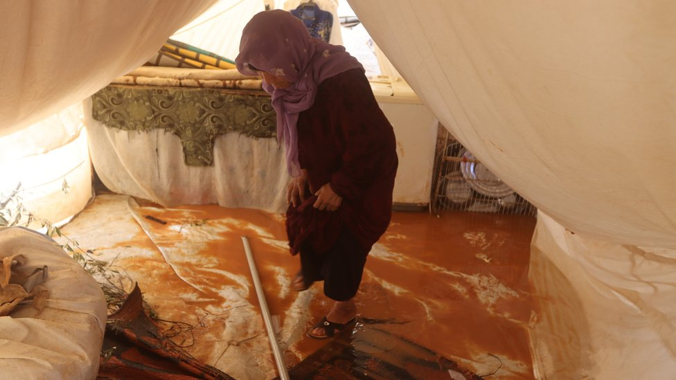 A woman stands in her flooded tent in Idlib province, Syria