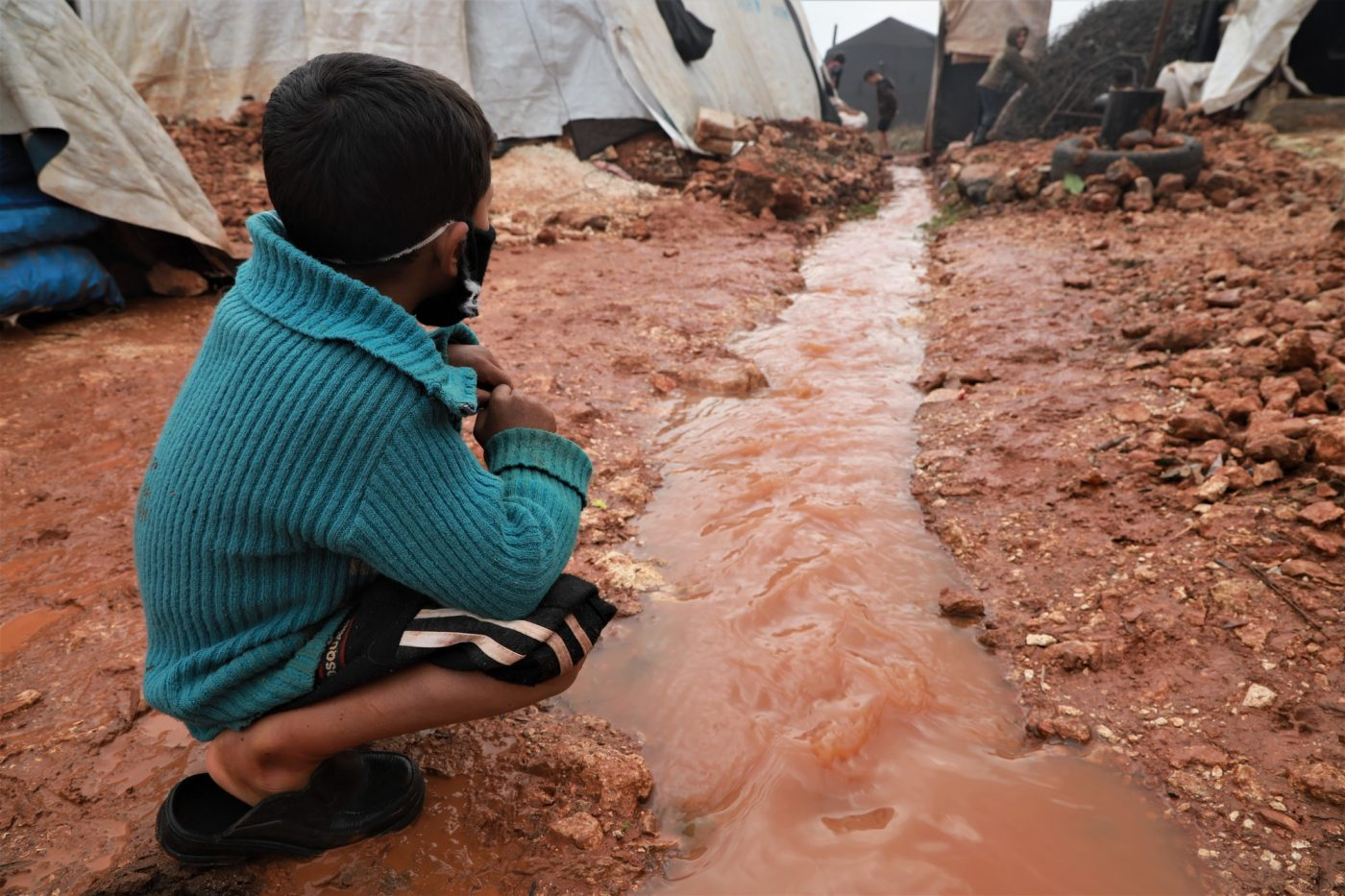 A boy looks at a water channel through a camp for displaced people in north-western Syria