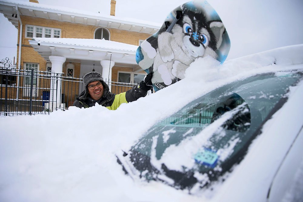 A man clears snow from his windscreen