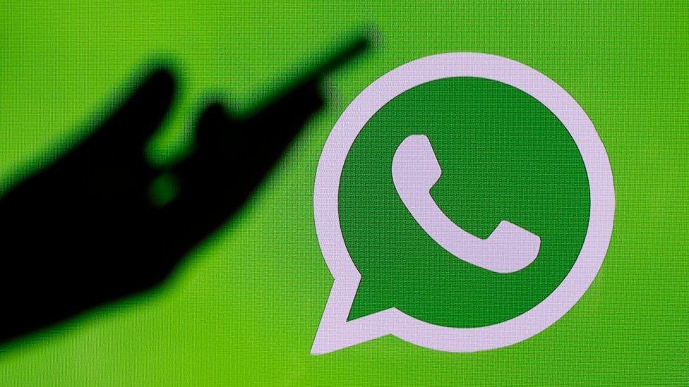 silhouette of hand holding phone next to WhatsApp logo