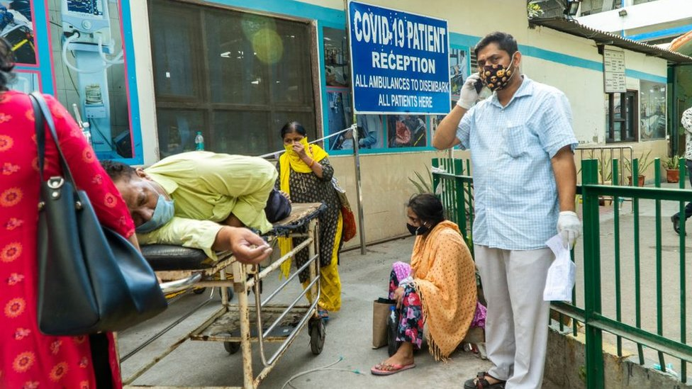 In this picture taken on April 23, 2021, relatives wait next to a Covid-19 coronavirus patient laying on a stretcher in a hospital complex for admission in New Delhi.