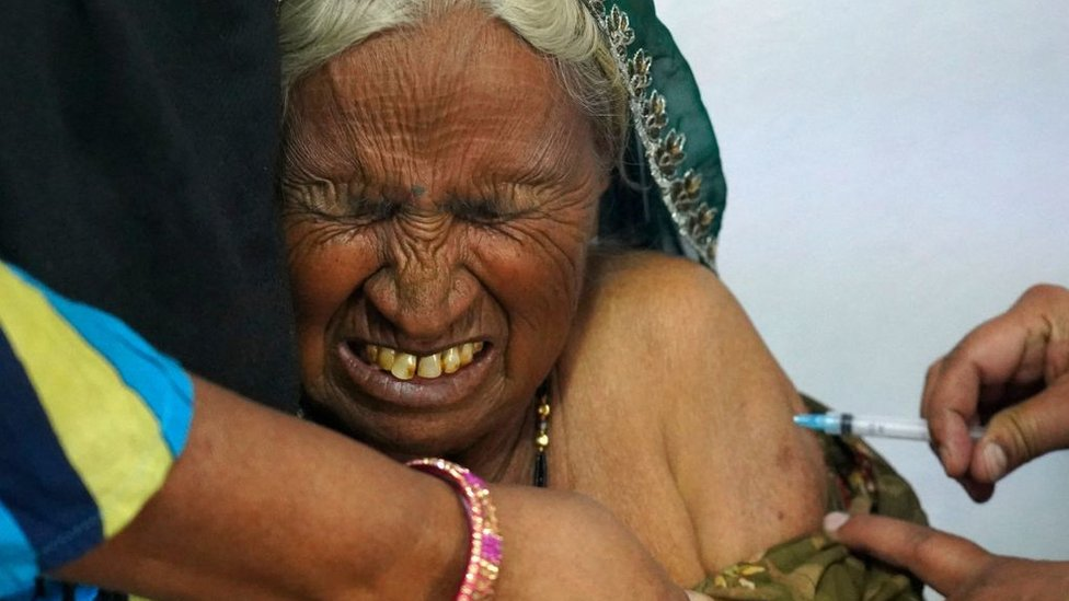 An elderly woman reacts as she is inoculated with the Covid-19 coronavirus vaccine at a government hospital on the outskirts of Ajmer