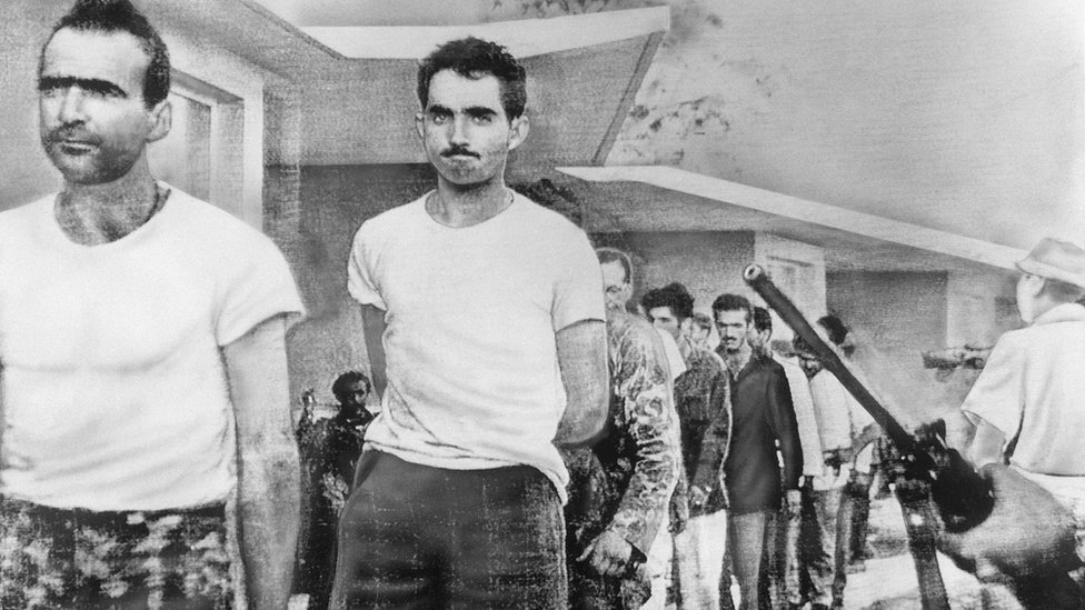 Watched by armed guards, grim-faced invaders are marched off to prison from temporary quarters at Giron Beach, Las Villas province, after their capture by Castro forces