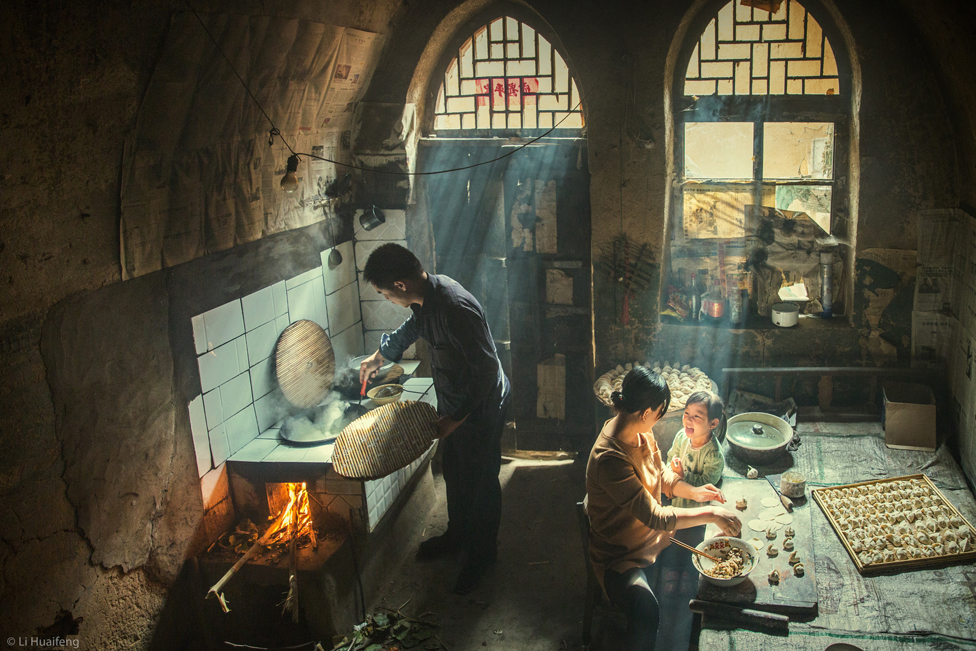 Family preparing food indoors, with rays of sunlight shining through the windows