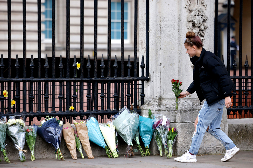 A woman adds a bunch of flowers to a line of floral tributes against the railings at the front of Buckingham Palace