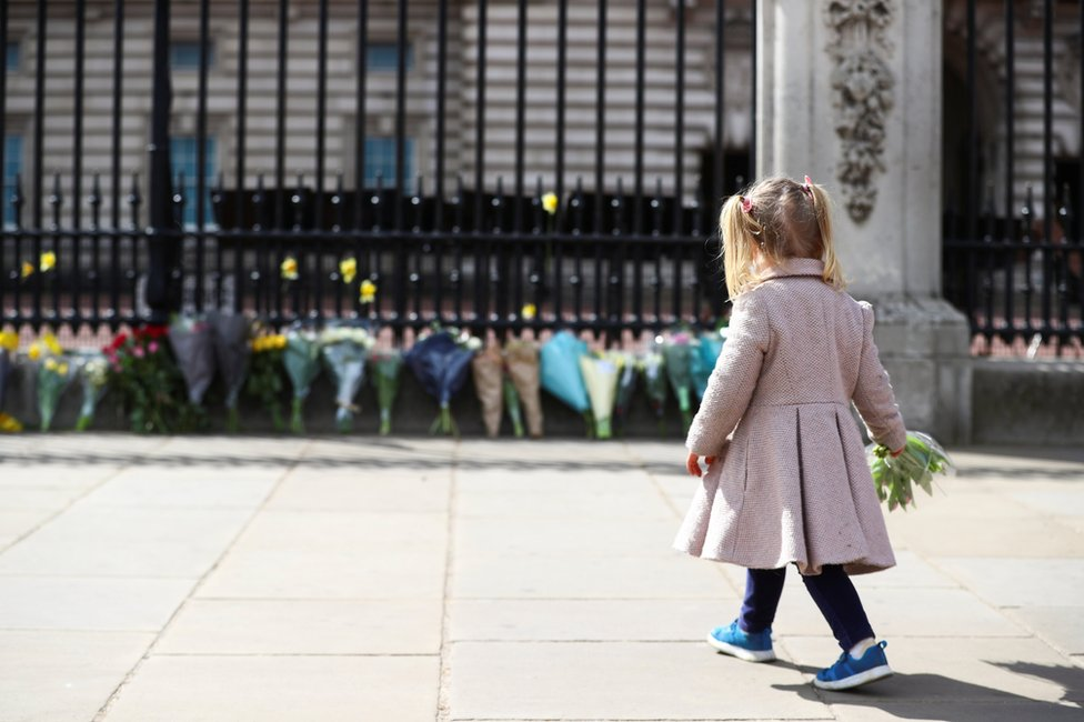 A little girl lays a bouquet of flowers outside Buckingham Palace