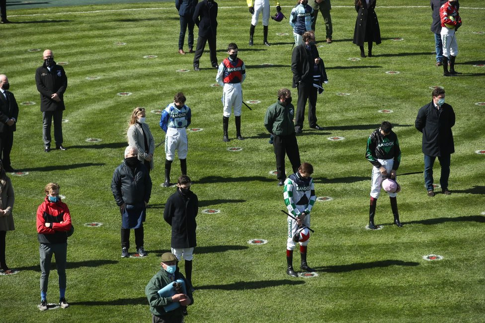 Racegoers and riders observe a two-minute silence for the late Prince Philip whilst social distancing