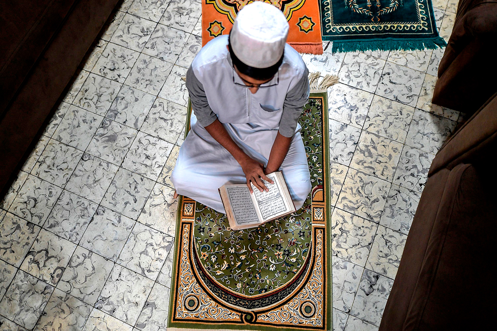A worshipper reads the Koran at his house