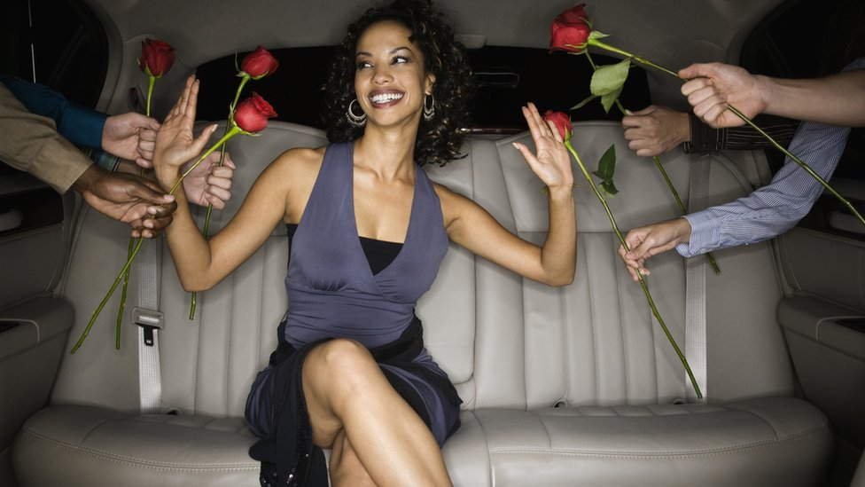 A woman sits in the back of a car while men offer her roses through the windows