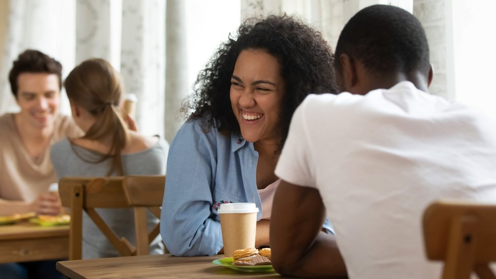 A woman laughs as she talks to a man at a speed dating event