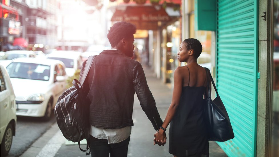 A man and a woman walk away from the camera down a city street
