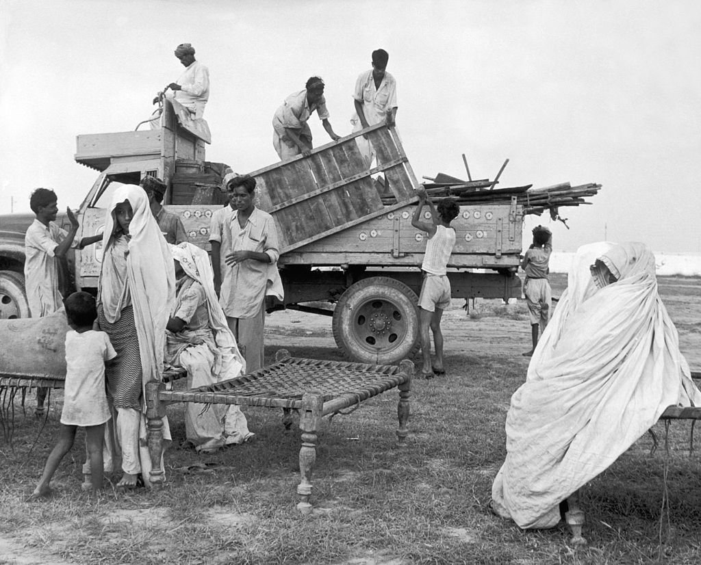 Korangi near Karachi : Muslim refugees from India unloading their belongings from a truck in a new colony built by the Pakistani government.