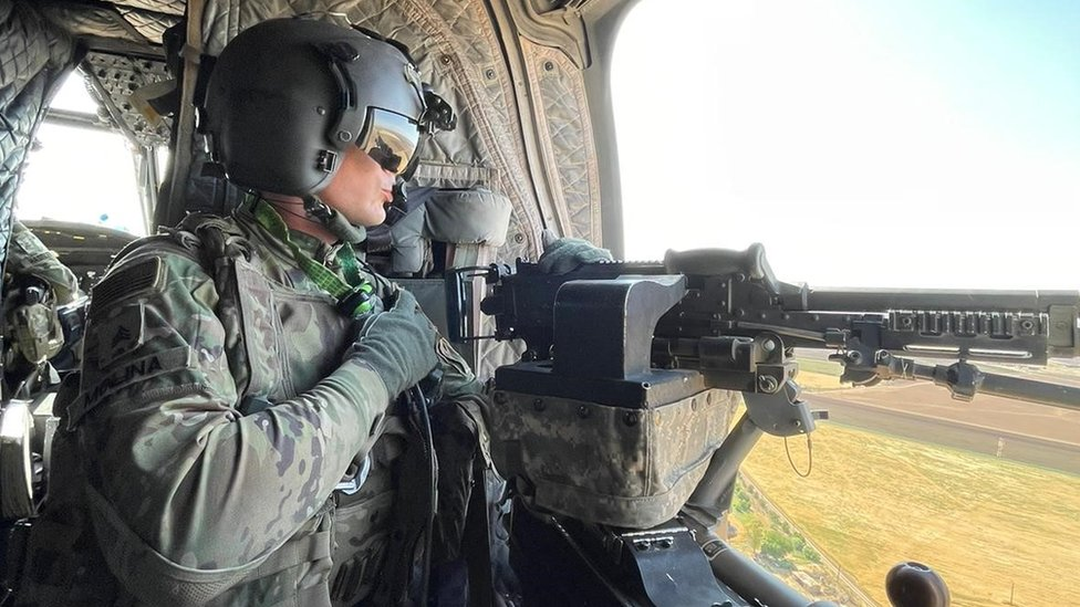 US service member holds a machine gun on board a helicopter. File photo