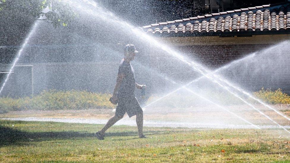 Sprinklers cool off a walker in North Hollywood on 28 June 2021.