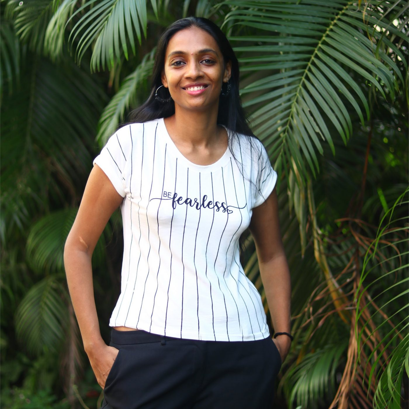 Pallavi standing by a tree with a t-shirt saying 'fearless' on it