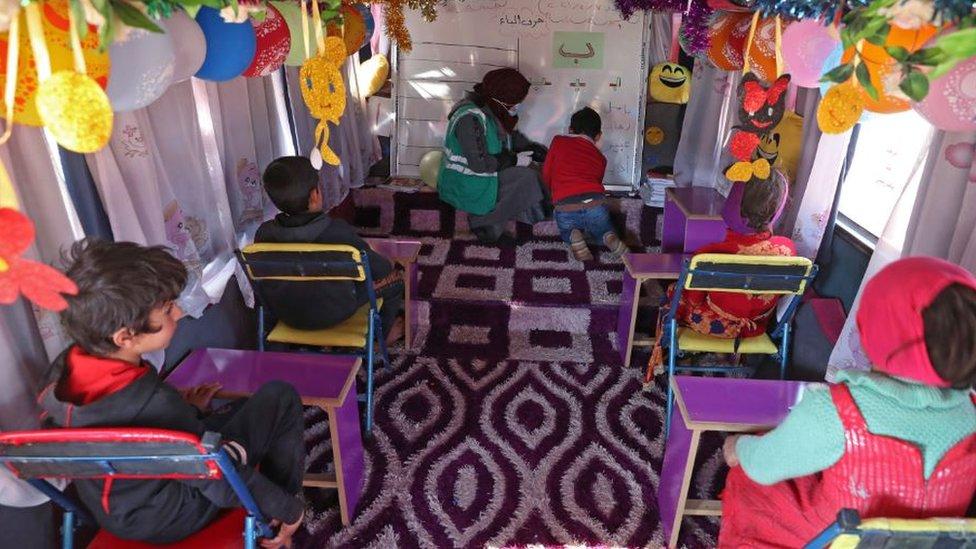 Children learning inside a bus