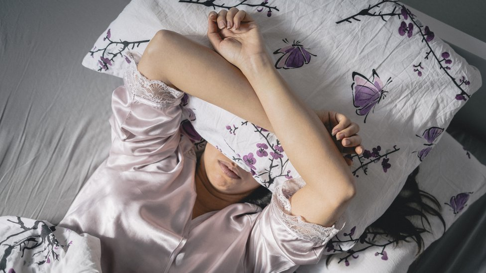 A woman struggling to get to sleep
