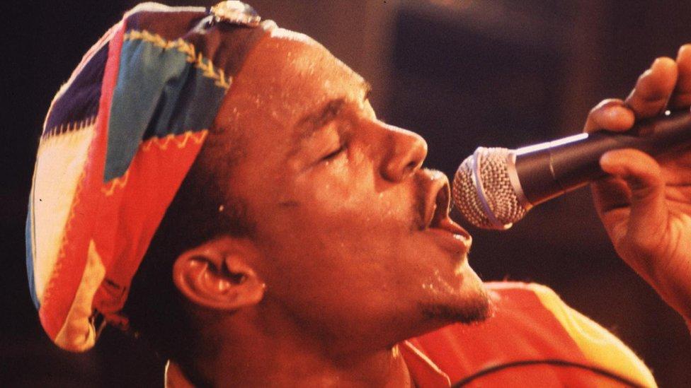 Andrew Tosh singing in reggae hat