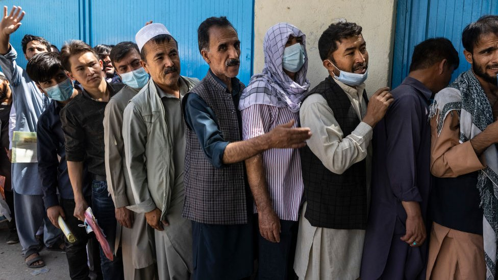 Afghans wait in long lines for hours at the passport office in Kabul