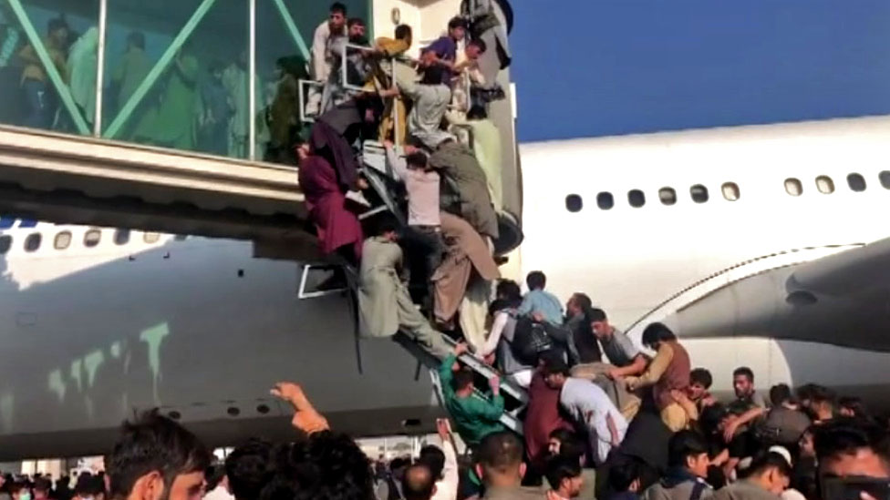 People climbing on to plane at Kabul airport