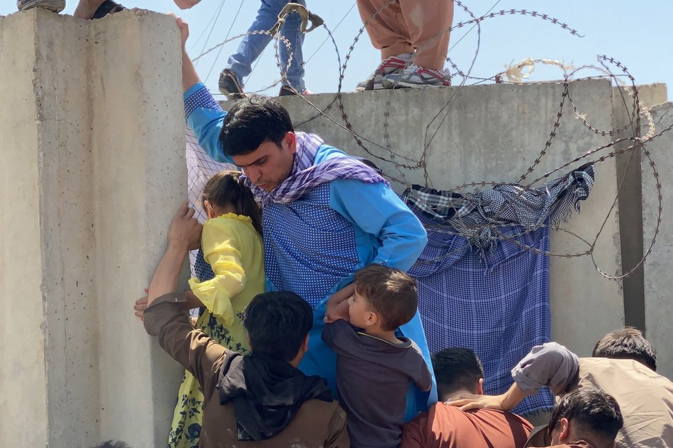 People struggle to cross the boundary wall of Hamid Karzai International Airport to flee Afghanistan on 16 August 2021