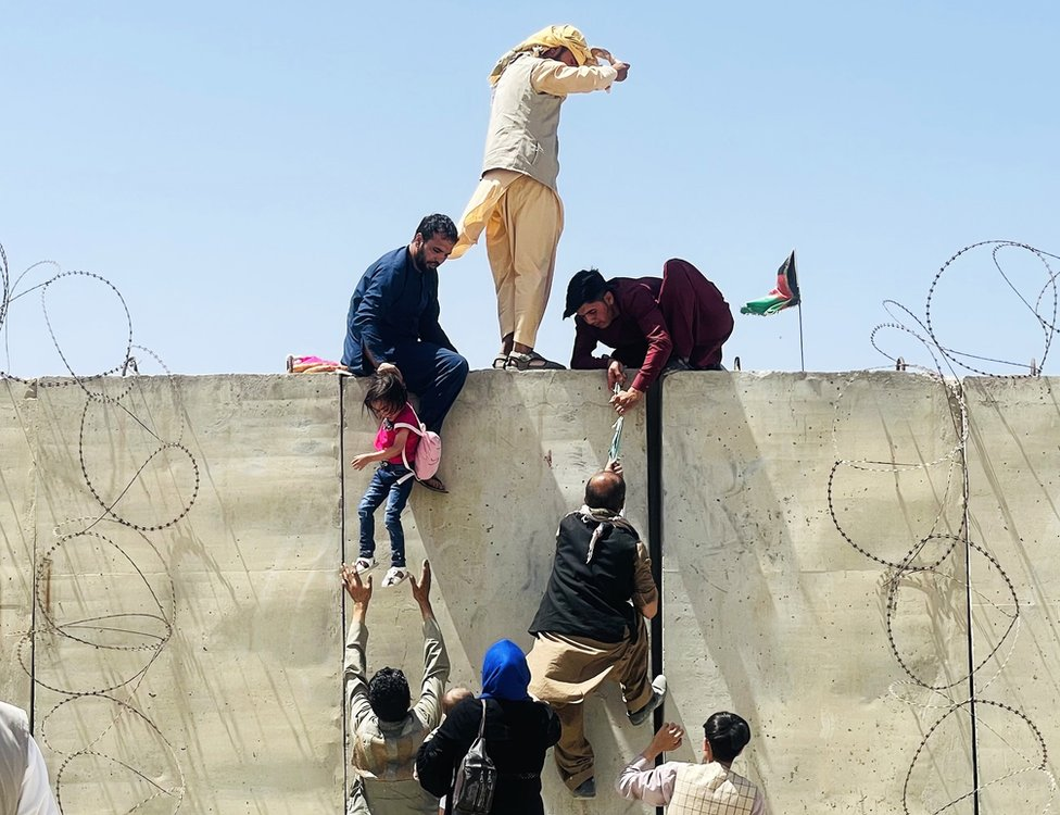 Thousands of Afghans rush to the Hamid Karzai International Airport as they try to flee the Afghan capital of Kabul, Afghanistan, on 16 August 2021