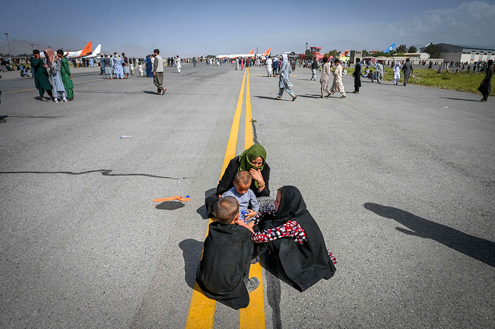 Afghan people sit on the tarmac as they wait to leave the Kabul airport in Kabul on 16 August 2021