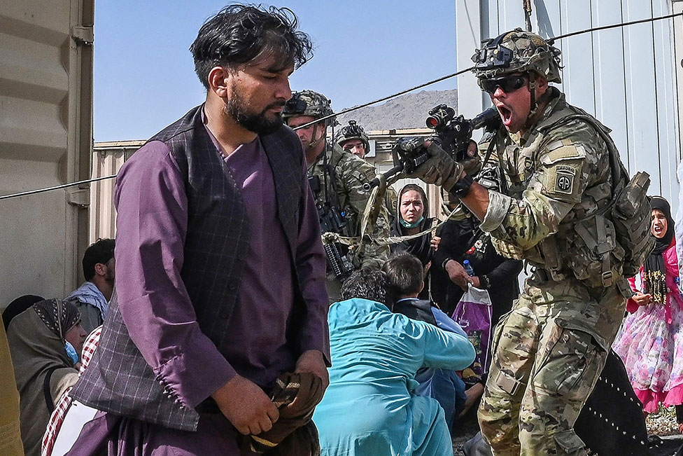 A US soldier points his gun towards an Afghan passenger at the Kabul airport in Kabul on 16 August 2021