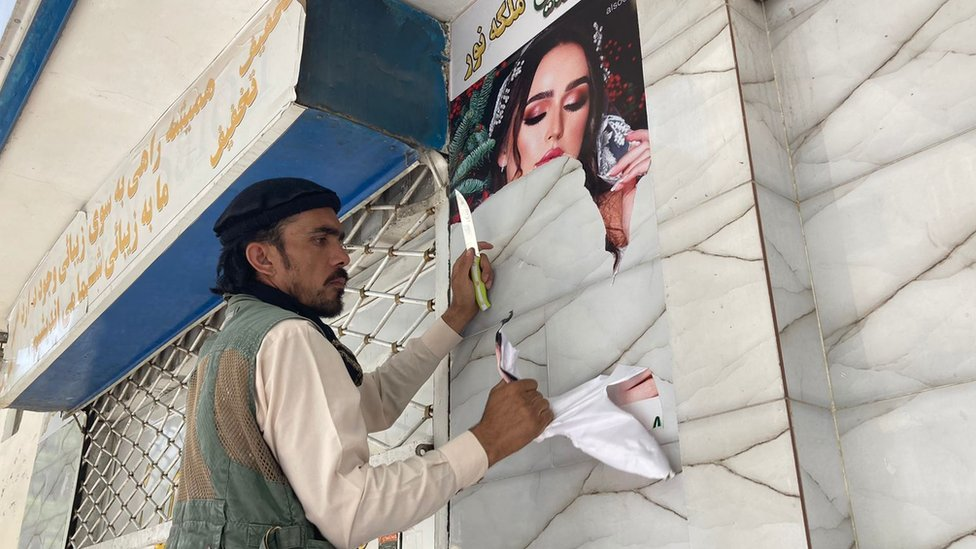 Pictures of an ad featuring a woman, being taken down in Kabul