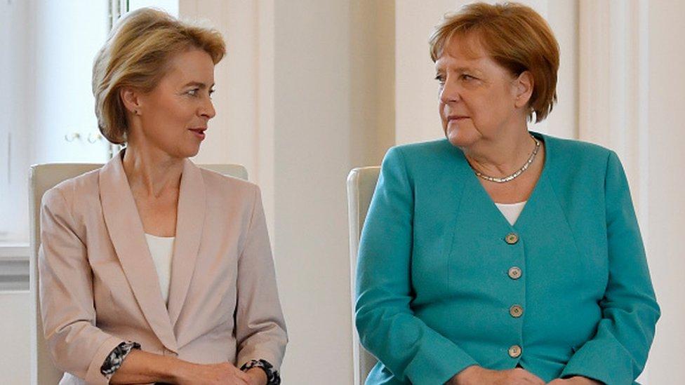 European Commission President Ursula von der Leyen sits next to German Chancellor Angela Merkel