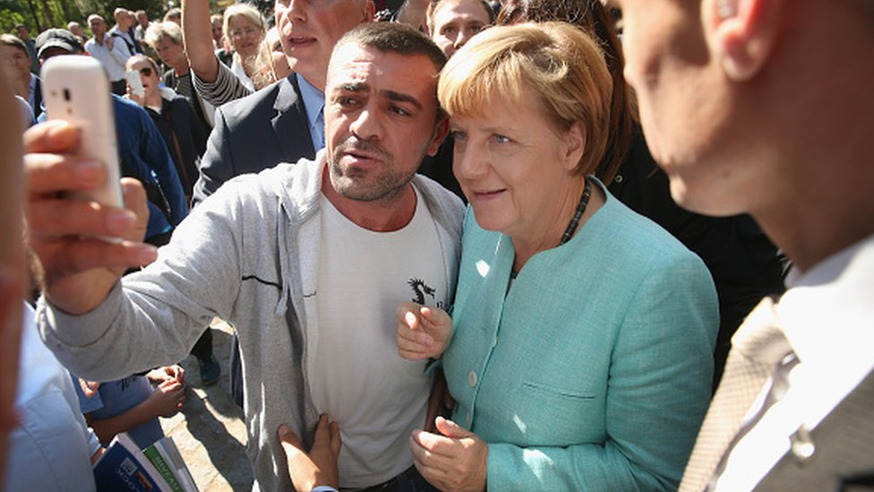German Chancellor Angela Merkel pauses for a selfie with a migrant