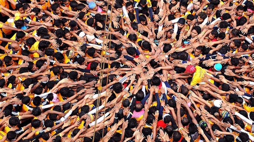 Indian Hindu devotees gesture before attempting to form a human pyramid in a bid to reach and break a dahi-handi (curd-pot) suspended in air during celebrations for the Janmashtami festival, which marks the birth of Hindu god Lord Krishna, in Mumbai on August 18, 2014.