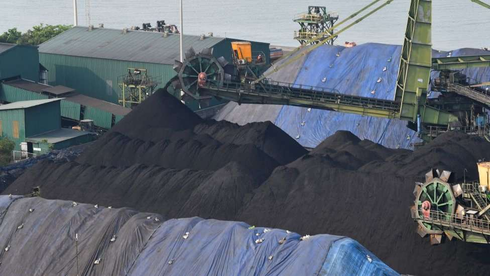 A shipment of coal is unloaded from a cargo vessel at the Mormugao Port Trust in Goa.