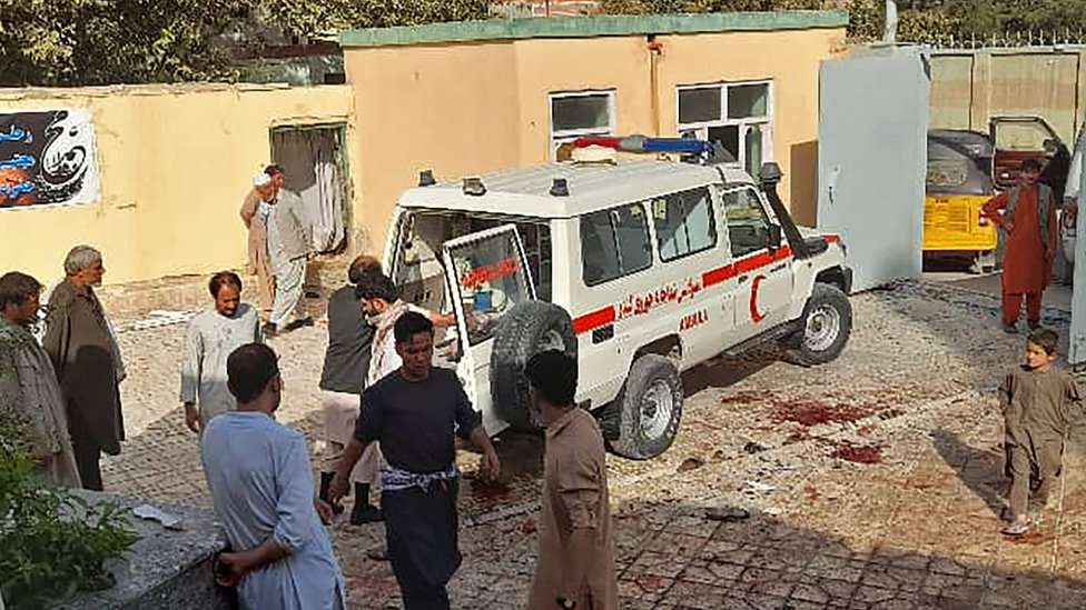 Afghan men stand next to an ambulance after a bomb attack at a mosque in Kunduz